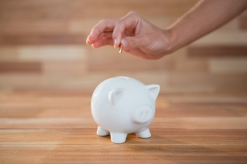 hand-inserting-coin-in-piggy-bank_1252-1125